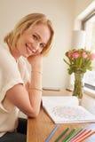 Mujer relajada con el libro de colorear adulto Foto de archivo libre de regalías