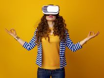 Mujer relajada contra la parte posterior del amarillo en auriculares de la realidad virtual Imagenes de archivo