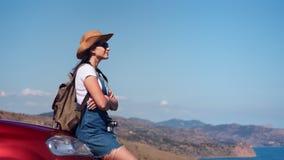 Mujer relajada del backpacker del viaje que admira el paisaje marino hermoso que se sienta en vista lateral del capo del coche almacen de metraje de vídeo