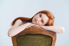 Mujer relajada del pelirrojo que se sienta en la silla Imagen de archivo libre de regalías