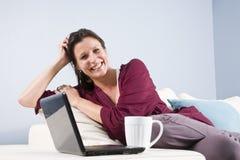 Mujer relajada en el sofá con la taza de la computadora portátil y de café imagen de archivo