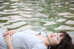 Mujer relajada en una orilla del agua imagen de archivo