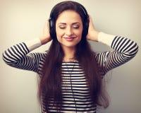 Mujer relajada feliz con los ojos cerrados que escucha la música en cabeza Imagen de archivo