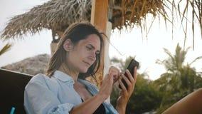 Mujer relajada feliz del viajero que usa el app del comercio electrónico del smartphone que sonríe, descansando en sillón de la p almacen de video