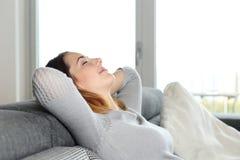 Mujer relajada feliz que descansa sobre un sofá en casa Fotos de archivo libres de regalías