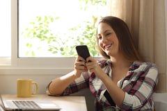 Mujer relajada feliz que manda un SMS en un teléfono móvil Fotografía de archivo libre de regalías