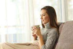 Mujer relajada pensativa que sostiene el café en casa Fotografía de archivo libre de regalías