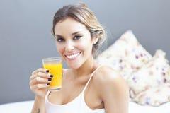 Mujer relajada que bebe el zumo de naranja en casa en dormitorio Imagen de archivo libre de regalías