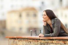 Mujer relajada que comtempla opiniones en un balcón foto de archivo libre de regalías