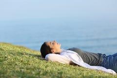 Mujer relajada que descansa sobre la hierba en la costa Fotos de archivo libres de regalías