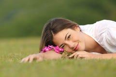 Mujer relajada que descansa sobre la hierba verde con las flores Foto de archivo