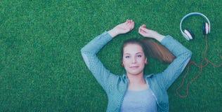 Mujer relajada que escucha la música con los auriculares que mienten en hierba Fotografía de archivo
