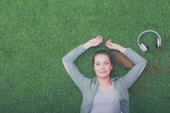 Mujer relajada que escucha la música con los auriculares que mienten en hierba Foto de archivo libre de regalías