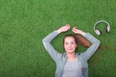 Mujer relajada que escucha la música con los auriculares que mienten en hierba Foto de archivo