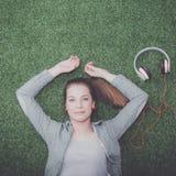 Mujer relajada que escucha la música con los auriculares que mienten en hierba Imagenes de archivo