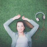 Mujer relajada que escucha la música con los auriculares que mienten en hierba Fotografía de archivo libre de regalías