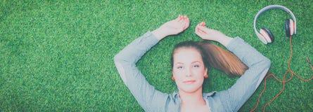 Mujer relajada que escucha la música con los auriculares que mienten en hierba Imagen de archivo libre de regalías
