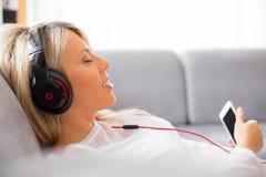 Mujer relajada que escucha la música en los auriculares en casa Fotos de archivo