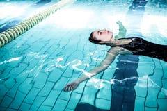 Mujer relajada que flota en la piscina Foto de archivo libre de regalías