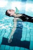 Mujer relajada que flota en la piscina Imagenes de archivo