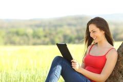 Mujer relajada que lee un ebook en el país Imagen de archivo