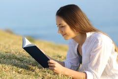 Mujer relajada que lee un libro de papel que miente en la hierba Foto de archivo libre de regalías