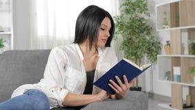 Mujer relajada que lee un libro en casa metrajes