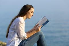 Mujer relajada que lee un libro que se sienta en la playa Imágenes de archivo libres de regalías