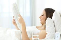 Mujer relajada que lee un periódico en la cama Fotografía de archivo