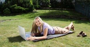 Mujer relajada que miente con el ordenador portátil Imagen de archivo libre de regalías