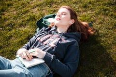 Mujer relajada que miente en césped y que escucha la música Imágenes de archivo libres de regalías