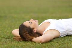 Mujer relajada que miente en la hierba que duerme en una escena tranquila Imagen de archivo libre de regalías