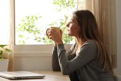 Mujer relajada que mira a través de una ventana en casa Foto de archivo