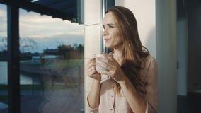 Mujer relajada que permanece cerca de ventana después de día laborable Bastante puesta del sol de observación de la señora almacen de video