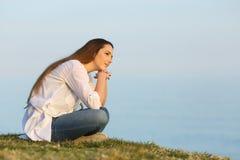 Mujer relajada que piensa y que mira lejos en la playa Imagen de archivo