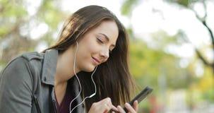 Mujer relajada que pone auriculares de botón y que escucha la música almacen de metraje de vídeo