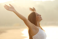 Mujer relajada que respira el aire fresco que aumenta los brazos en la salida del sol