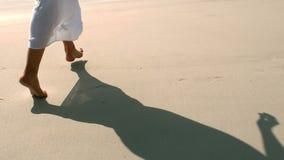 Mujer relajada que salta en la arena almacen de metraje de vídeo