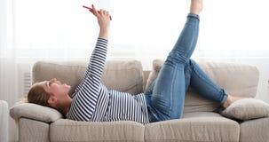 Mujer relajada que sopla un beso mientras que vídeo que charla en el teléfono metrajes