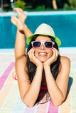 Mujer relajada que toma el sol en la piscina Foto de archivo