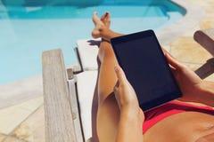 Mujer relajada que usa la tableta digital por el poolside Imagen de archivo libre de regalías