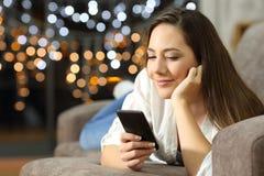 Mujer relajada que usa un teléfono elegante que miente en un sofá Fotos de archivo