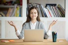 Mujer relajada tranquila que medita con el ordenador portátil, ninguna tensión en el trabajo
