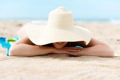 Mujer relajante con Sunhat en la playa imagenes de archivo