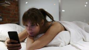 Mujer relajante en película de observación de la cama en Smartphone en la noche almacen de video