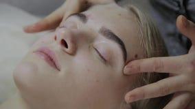 Mujer relajante que tiene un masaje para su piel en una cara en salón metrajes