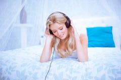 Mujer reservada que disfruta de una cierta música en su dormitorio Foto de archivo