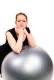 Mujer resuelta que se inclina sobre una bola de los pilates Fotografía de archivo