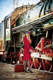 Mujer retra con la maleta en la estación de tren. Foto de archivo