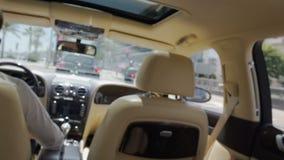 Mujer rica joven que viaja en coche, chófer privado que conduce el auto costoso metrajes